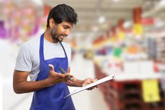 Supermarket employee looking at clipboard. Indian supermarket or hypermarket male employee looking at clipboard as planning with serious expression royalty free stock image