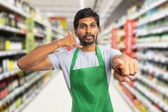 Supermarket employee making call us gesture royalty free stock photo