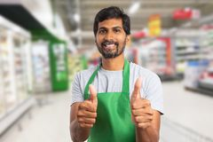 Supermarket employee making thumb-up gesture. Indian male supermarket or hypermarket employee making thumb-up gesture as like or agree concept wearing green royalty free stock photo