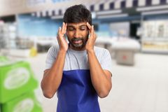 Supermarket employee with migraine. Indian supermarket or hypermarket employee man with migraine using fingers for touching temples as stress concept royalty free stock photos