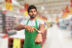 Supermarket employee pointing at watch as you are late concept. Upset indian male supermarket employee or manager with serious expression pointing with index royalty free stock photos