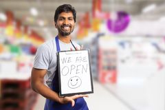 Supermarket employee presenting clipboard with we are open text. Friendly indian supermarket or hypermarket employee presenting clipboard with we are open text stock photos