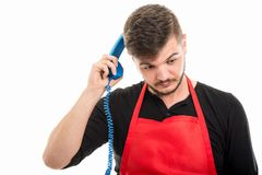Supermarket employer scratching with blue phone receiver like th Royalty Free Stock Image