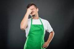 Supermarket employer standing acting tired. Supermarket employer standing with eyes closed acting tired on black background stock photos