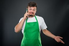Supermarket employer talking at phone gesturing not knowing Royalty Free Stock Photo