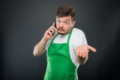 Supermarket employer talking at phone gesturing not knowing Stock Photos