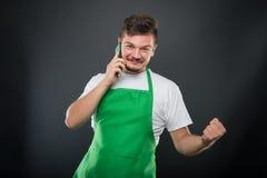 Supermarket employer talking at phone gesturing winning Stock Photo