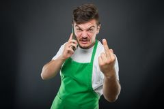 Supermarket employer talking at phone showing obscene gesture. On black background Royalty Free Stock Photos