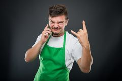 Supermarket employer talking at phone showing rock on gesture. On black background Royalty Free Stock Photos