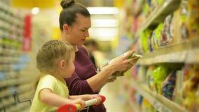 supermarket för dottermodershopping De köper flingor för en frukost Ett dottersammanträde i en supermarket stock video