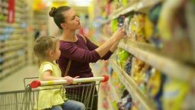 supermarket för dottermodershopping De köper flingor för en frukost Ett dottersammanträde i en supermarket lager videofilmer