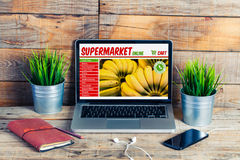 Supermarket grocery online shop in a laptop screen at the office. Grocery online shop website in a computer display stock photography