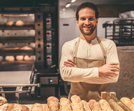 At the supermarket. Handsome supermarket worker is looking at camera and smiling while standing near the bakery Royalty Free Stock Photography