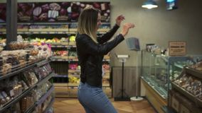 At the supermarket: happy young girl funny dancing between shelves in supermarket. Blonde girl wearing jeans and black