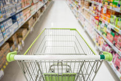Supermarket interior, empty green shopping cart. Stock Images