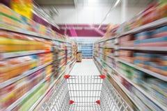 Supermarket interior, empty green shopping cart. Stock Photos