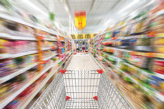 Supermarket interior, empty shopping cart. Royalty Free Stock Images