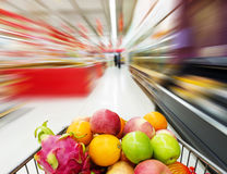 Supermarket interior, filled with fruit of shopping cart. Stock Images