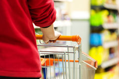 Supermarket. Lady pushing a shopping cart in the supermarket royalty free stock images