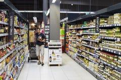 Supermarket med hyllor av mat och drycker Merkur i Österrike Fotografering för Bildbyråer