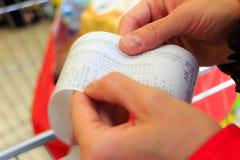 supermarket papierowy czeka kwitu rachunek w ręce Obraz Royalty Free