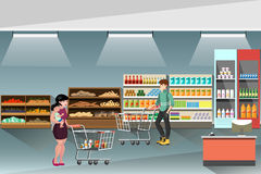 Supermarket, with people shopping and buying products on shelves. People with shopping carts buy food in the supermarket Royalty Free Stock Photography