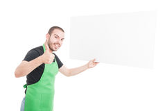 Supermarket seller showing thumb up and holding big advertising stock photography