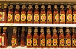 A supermarket shelf with all gold tomato ketchup bottles.  royalty free stock photography