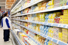 Supermarket shelves. Women are shopping for milk products between the shelves, inside a supermarket Stock Photography