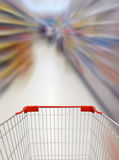 Supermarket shelves aisle blurred background with shopping cart Royalty Free Stock Photos