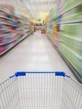 Supermarket shelves aisle blurred background Stock Images