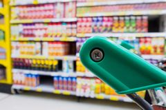 Supermarket shelves. With shopping cart Royalty Free Stock Photos
