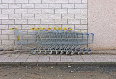 Supermarket shopping trolleys by wall Royalty Free Stock Images