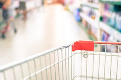 Supermarket store blurred background with close up shopping cart. And bokeh light royalty free stock photography