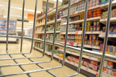 Supermarket trolley basket view. Photo of a supermarket isle and food shelves view from inside the customers basket or trolley Royalty Free Stock Photography