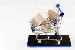 Supermarket trolley with boxes on white background. Copy space.  royalty free stock photography