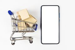 Supermarket trolley with boxes on white background. Mockup smartphone with blank screen, can be add your texts or others royalty free stock photo