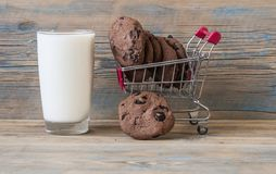 Supermarket trolley with cookies. Sweet chocolate cookies in trolley on wooden background Royalty Free Stock Photos