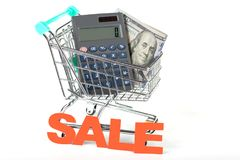 A supermarket trolley with dollars and a calculator. Concept - sales and discounts. Advantageous purchases and savings Stock Image