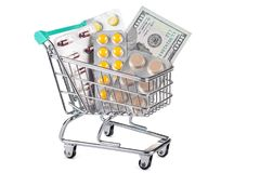 A supermarket trolley with dollars and pills. Concept - sales and discounts for medicines. Shopping in the pharmacy Stock Images
