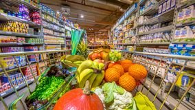 Supermarket trolley with fruit and vegetables. Grocery shop cart in supermarket filled up with fresh and healthy food products as seen from the customers point Royalty Free Stock Photo