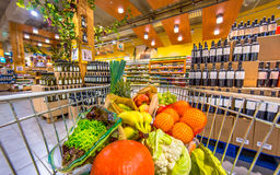 Supermarket trolley with fruit and vegetables on wine section. Grocery shop cart in supermarket filled up with fresh and healthy food products on the wine and Stock Image