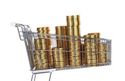 Supermarket trolley full of very big golden coins stacks. Side view on white background Stock Image