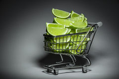Supermarket trolley with slices of lime Royalty Free Stock Photos