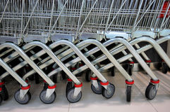 Supermarket trolleys. Row of metal trolleys in a supermarket Royalty Free Stock Images