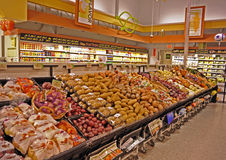 Supermarket vegetable and fruit section. Oranges, red potatoes, white  potatoes, sweet potatoes, onions, pumpkins, squash, fruit juice, and more in a supermarket Royalty Free Stock Photography