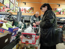 Supermarket week end shopping. Bucharest, Romania, December 24, 2015: People are putting their products in a cart in a supermarket in Bucharest Royalty Free Stock Photography