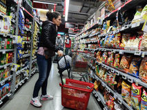 Supermarket week end shopping. Bucharest, Romania, December 24, 2015: A woman is shopping between the shelves, in the aisle inside a supermarket in Bucharest Royalty Free Stock Photography