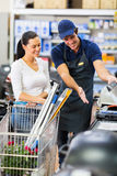 Supermarket worker customer. Supermarket worker help female customer in buying bbq grill Royalty Free Stock Photos