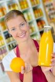 Supermarket worker holding bottle orange juice Royalty Free Stock Photo